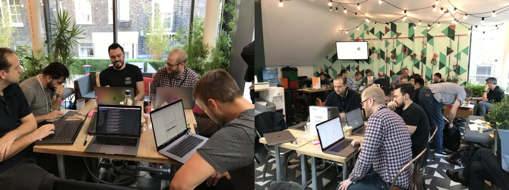 A team of developers with laptops gathered around a table