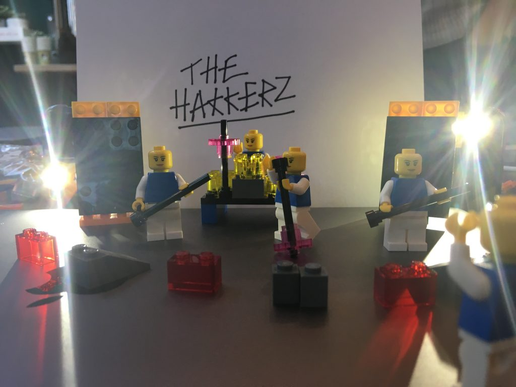 Four lego people in a band called The Hakkerz with musical equipment and lighting